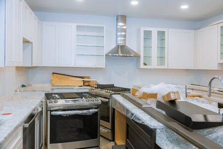 Interior of modern kitchen with all appliances on stove top, marble counter with kitchen white cabinets