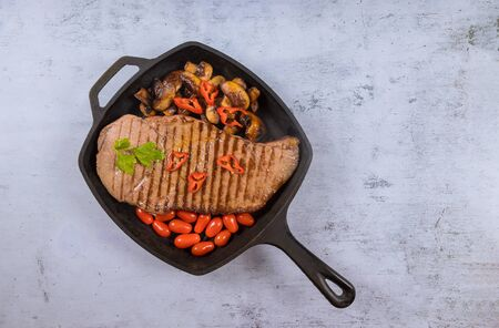 Grilled beef sirloin steaks with vegetable and mushrooms in grill pan.