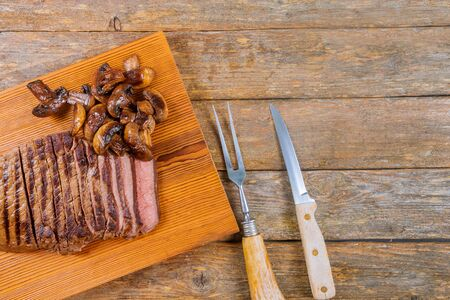 Sliced grilled beef with mushrooms on wooden board.