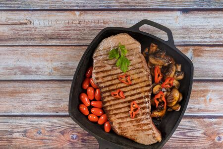 Beef steak lies on a black grill pan with mushrooms.