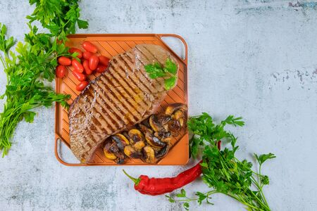 Grilled beef with mushrooms and tomato on griddle. Stockfoto