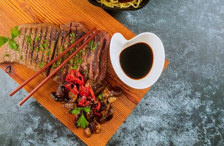 Grilled beef steak with chopstick on cutting board. Top view. Stockfoto - 130813613