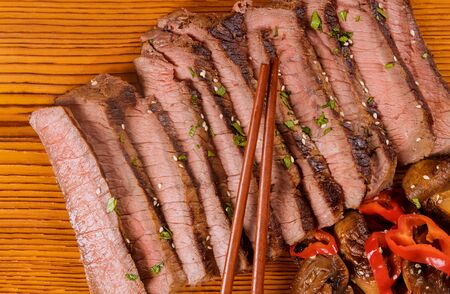 Grilled beef slised on cutting board with chopstick. Top view.