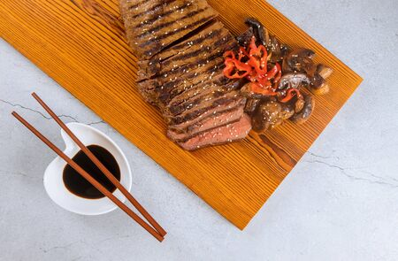 Grilled beef steak with chopstick on cutting board. Top view. Stockfoto - 130813624