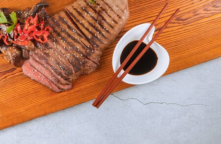 Delicious beef steak on wooden board with soy sauce.