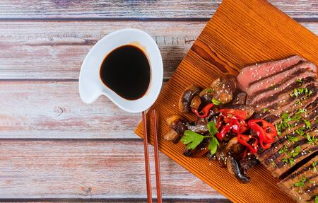 Beef korean grilled beef, red chilli peppers and mushrooms on wooden board with chopsticks. Stockfoto