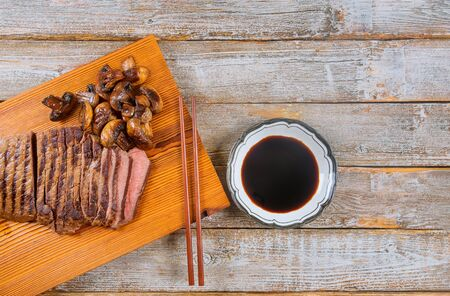Grilled beef steak medium rare on wooden cutting board with soy sauce. Stockfoto - 130813690