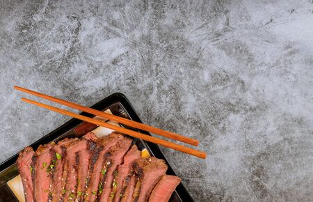 Grilled beef sliced with chopstick on black plate.