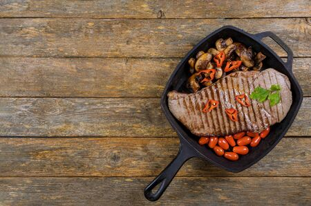 Beef steaks with grilled mushrooms in grill pan on wooden background. Stockfoto - 130813697