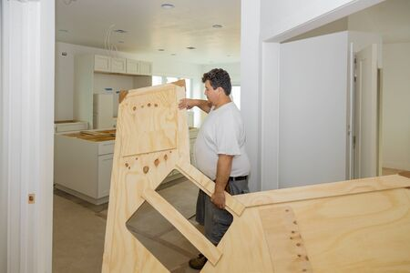 Carpenter installing c counter top in a kitchen remodel.