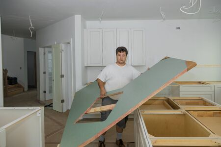 Carpenter installing cabinets a laminate counter top in a kitchen furniture for home improvement