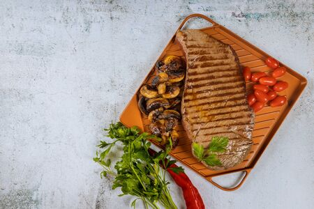 Grilled beef steak with mushrooms and herbs on iron griddle. Stockfoto