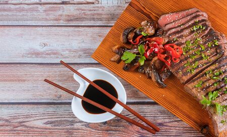 Sliced grilled beef with mushrooms and chilli pepper on cutting board.