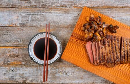 Grilled beef medium rare on a wooden cutting board with soy sauce.