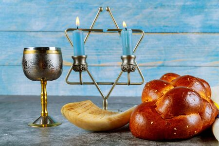 Shabbat challah bread, shabbat wine and candles on the table.