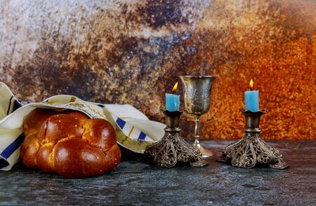 Jewish Holiday shabbat eve with challah bread, Sabbath candles and kiddush wine cup.