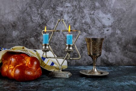 Sabbath Jewish Holiday homemade sesame challah bread and candelas on table Reklamní fotografie