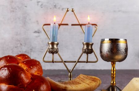 Shabbat Jewish holiday with challah bread on a candles and cup of wine. Reklamní fotografie