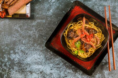 Catelli noodles with vegetables, beef and chopstick. Asian food.
