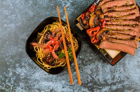 Korean spaghetti Catelli with grilled beef, mushrooms and chopstick.