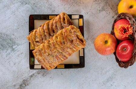 Apple strudel on square plate with apples on white table. Reklamní fotografie