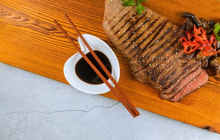 Sliced medium rare grilled beef with soy sauce and chopstick on cutting board.