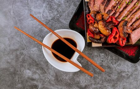 Beef, mushrooms and soy sauce with wooden chopstick. Stockfoto