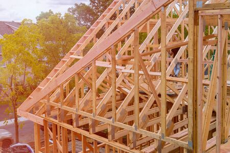 Panorama of modern condominium building with under construction wooden house with timber framing, truss, joist, beam close-up