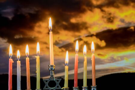 Jewish holiday Hanukkah with menorah traditional burning candles beautiful sunset sky in twilight background Banco de Imagens - 130814142