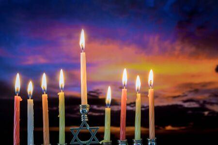 Jewish holiday symbol Hanukkah menorah sunset sky clouds twilight sky.