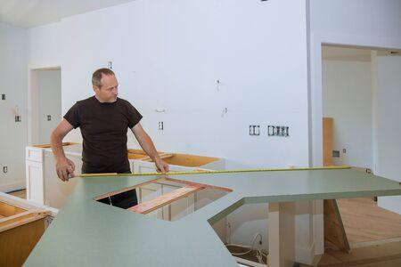 Hombre con cinta métrica para medir sobre encimera de cocina de madera en muebles para mejoras para el hogar.