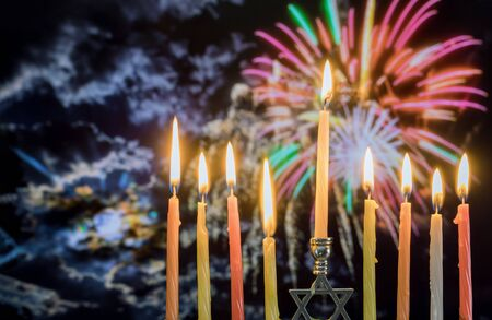 Hanukkah menorah with candles, twilight colorful firework sky background Banco de Imagens - 130814237