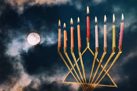 Jewish holiday Hanukkah menorah with sparks on full moon in the clouds background