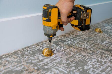 Door stopper installed with carpet floor in using screwdriver 스톡 콘텐츠