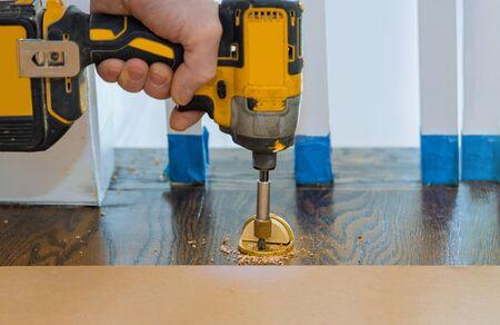 Metal modern professional installing door stopper on wooden floor in using screwdriver