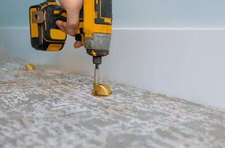Builder in installing doorstop in a modern house, in using screwdriver a new house 스톡 콘텐츠