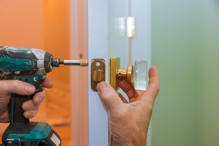 Closeup of a professional locksmith installing or new lock on a house door handle with screwdriver Stockfoto