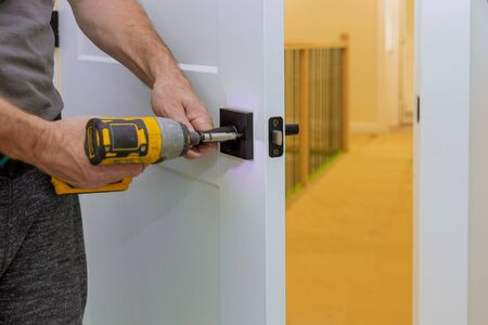 Handyman installing the door lock in the room with screwdriver, Close-up of new a house on the open door Stockfoto