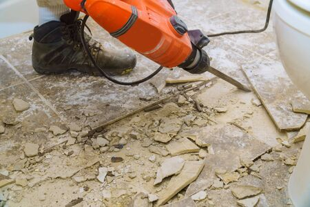 Renovation of old floor demolition old tiles with bath jackhammer Stockfoto