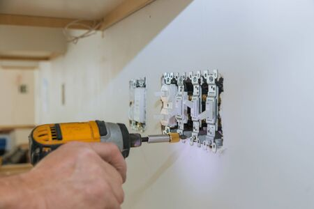 Work on installing electrical outlets with electrical wires and connector installed in plasterboard drywall