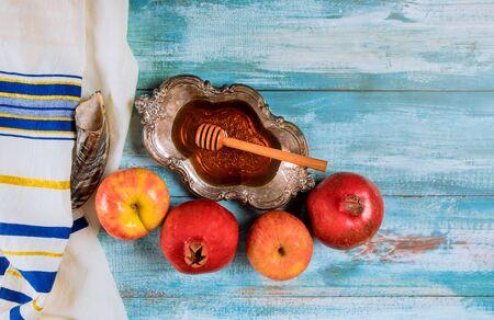 Honey on the pomegranate and apples. Jewish new year Yom Kippur and Rosh Hashanah kippah yamolka and shofar Orthodox Jewish prays