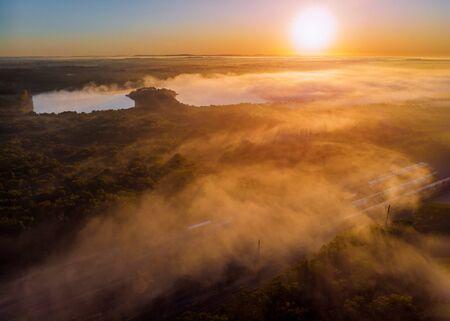 Beauty fantastic foggy lake with sunlight sun beams through tree dramatic colorful scenery. Banco de Imagens