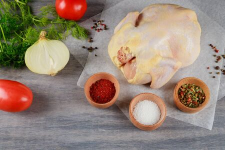 Ingredients for the soup broth in raw whole chicken, carrots, celery, on rustic wooden background Reklamní fotografie