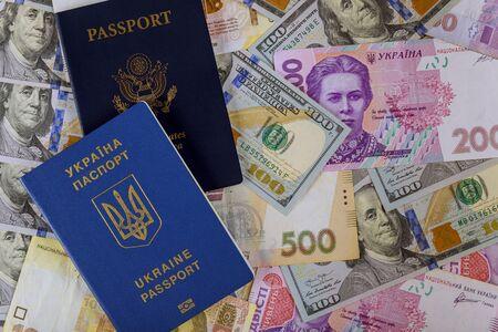 Dual citizens US Passport and ukrainian biometric passpor of US dollar money and ukrainian money hryvnia Stock Photo