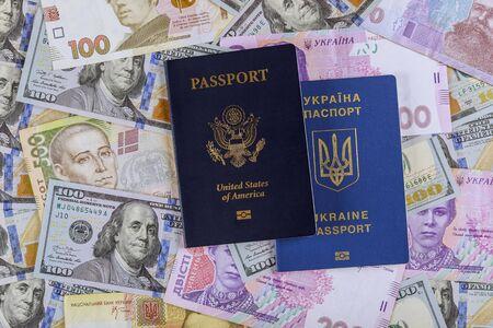 Dual citizens US and Ukrainian passports of US Ukrainian currency money dollar hryvnia banknotes