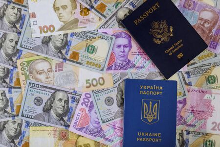 New blue Ukrainian electronic passport of dual citizens and American passpor let Ukrainian hryvna, American banknotes dollar bill