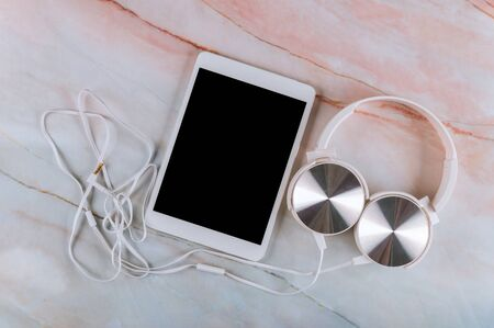 Modern headphones and digital table on marble table. Space for text Imagens