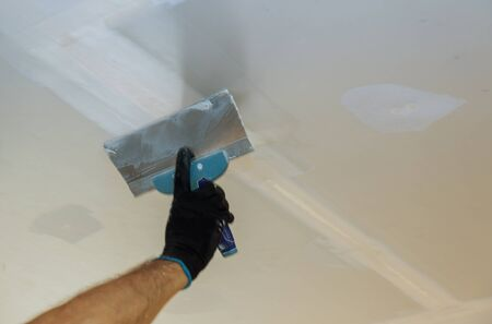 Male builder repairs wall with a spatula plaster on a wall