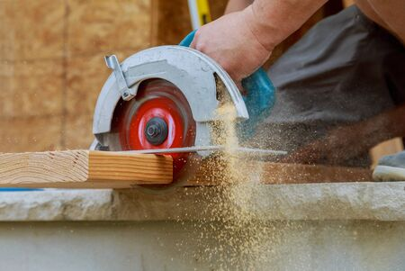 New home constructiion project building contractor worker using hand held worm drive circular saw to cut boards Stockfoto