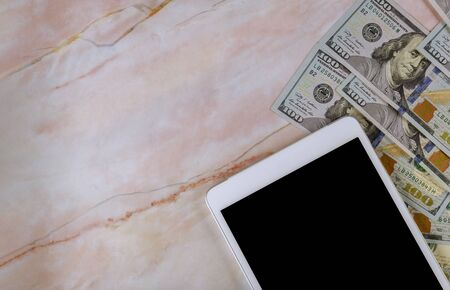 Digital tablet computer with isolated screen in over cash money american dollars in marble background